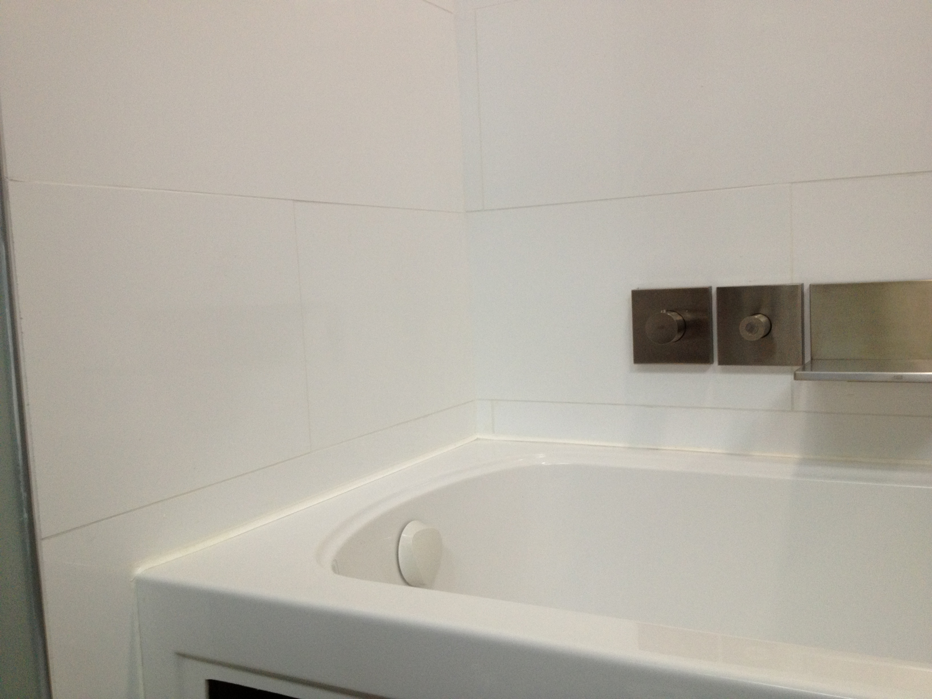 Clean, white bathroom tile – Lux Design and Contracting